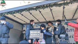 """Ex-Polizist Hilz wird in München direkt beim Reden von der Bühne abgeführt beim """"Demo-Fasching""""."""