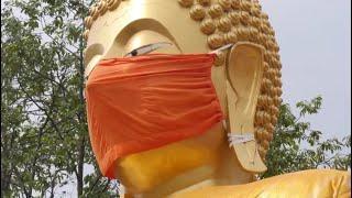 Corona-Wahnsinn - Buddha-Statue in Thailandmit Mundschutz